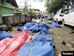 Dead bodies are seen, Sept. 29, 2018, on a street after earthquake hit in Palu, Indonesia.