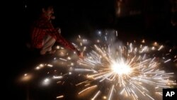 In this Sunday, Oct. 30, 2016 photo, an Indian lights firecrackers to celebrate Diwali, the Hindu festival of lights, in Jammu, India. Hindus across the country are celebrating Diwali where people decorate their homes with light and burst firecrackers.