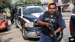 A municipal police officer during a confrontation with members of a gang in the beach resort of Acapulco, Mexico, 8 Jan 2011.