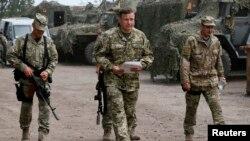 Menteri Pertahanan Ukraina Valery Heletey (tengah) berjalan bersama para tentara di markas sementara dekat kota Slovyansk (6/7).