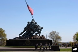 FILE - National Park Service rangers walk toward the U.S. Marine Corps War Memorial in Arlington, Virginia, April 29, 2015.