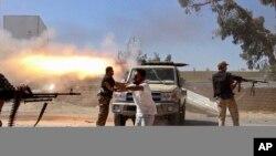 Des combattants islamistes de la Brigade Misarata tirent en direction de l'aéroport de Tripoli dans une tentative d'arracher le contrôle d'une puissante milice rivale à Tripoli , Libye, 26 juillet 2014.