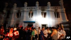Anggota Palang Merah Burma dan warga berkumpul di depan masjid yang kebakaran di Ranggon (2/4). 13 anak-anak dilaporkan menjadi korban yang tewas dalam kebakaran ini.