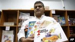 Họa sĩ biếm họa Zulkiflee Anwar Haque, còn được biết với tên Zunar cầm các quyển sách khôi hài bị cấm ở Malaysia.