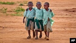 FILE - Young schoolboys walk home in the village of Nyumbani, Kenya, which caters to children who lost their parents to HIV, and grandparents who lost their children to HIV.