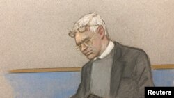 Julian Assange wearing two pair of glasses in seen in court during a hearing to decide whether he should be extradited to the United States, in London, Feb. 24, 2020 in this courtroom sketch.