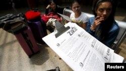 一名哥倫比亞醫療工作者在波哥大公交車總站向乘客散發預防寨卡病毒傳播的信息。 (2016年1月31日)