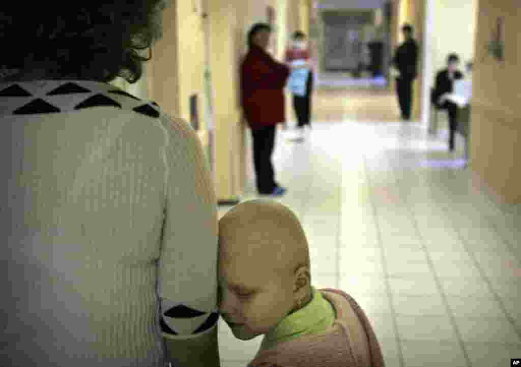 Vika Chervinska, an eight-year-old Ukrainian cancer patient, waits with her mother to receive treatment at the Kiev children's hospital in 2006. (AP Photo/Oded Balilty)