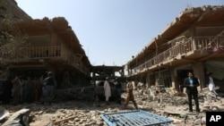 Warga berkumpul di lokasi serangan bom mobil di Kabul, Afghanistan (7/8). (AP/Rahmat Gul)