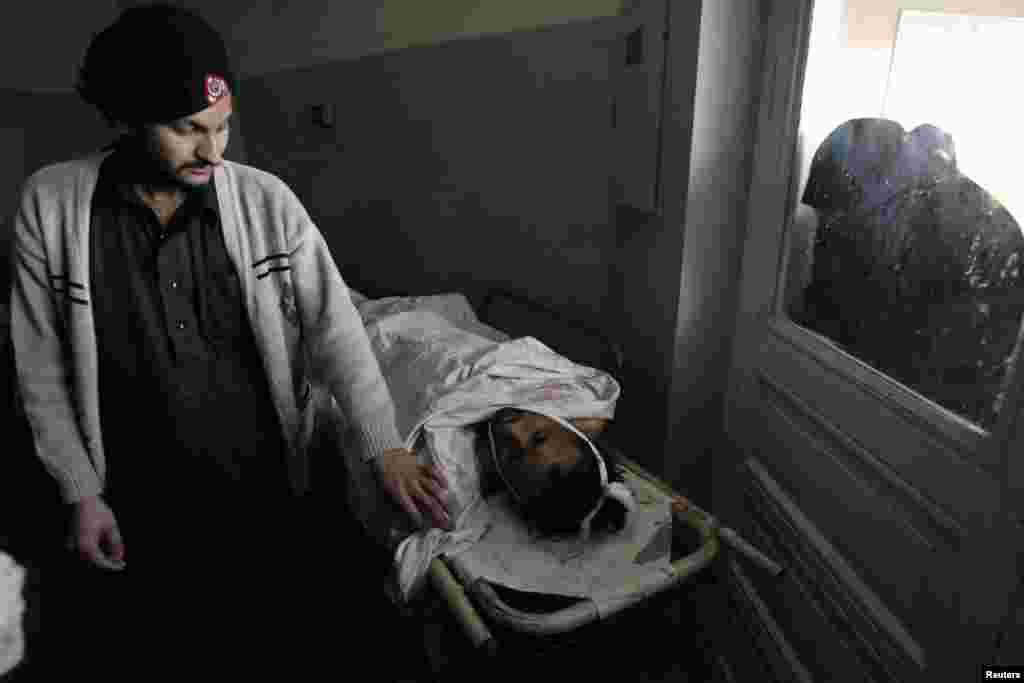 A woman looks through a window while a man who was wounded in a bomb attack at Fauji Market lies at the Hayatabad hospital in Peshawar, Pakistan, December 17, 2012.