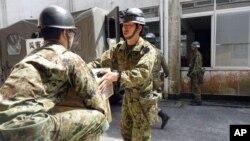 Tentara Jepang membawa perlengkapan untuk membangun tempat penampungan sementara bagi pengungsi gempa di Minamiaso, Kumamoto, Jepang selatan (19/4).
