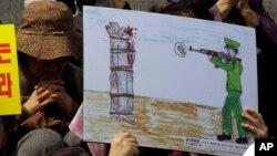 지난 2011년 4월 서울에서 열린 북한 인권 시위에서 한 탈북자가 공개 사형집행 그림을 들고 있다. (자료사진)