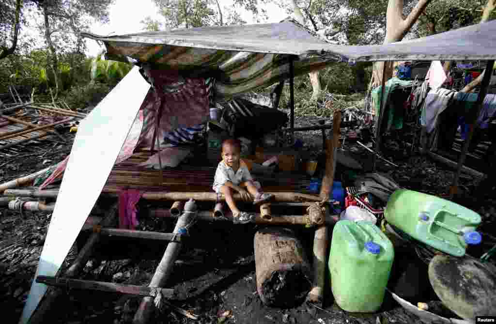 A child sits amid the remains of a house destroyed by Typhoon Rammasun in Batangas city, south of Manila, July 17, 2014.