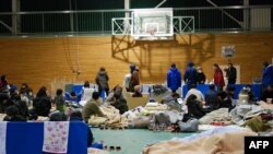 Những người di tản tụ tập ở sân bóng rổ của trường trung học Koriyama, tỉnh Fukushima, Nhật Bản, 16/3/2011