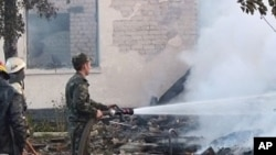 In this image released by the Ukraine Emergency Situations Ministry firefighters work to extinguish a fire as smoke rises above the ruins of an old peoples home in the Bile village in the Rivne region in western Ukraine some 300 kilometers (180 miles) wes