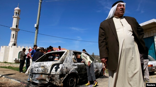 A Palestinian stands near a burnt car in the West Bank village of Kusra, near Nablus, February 21, 2013.