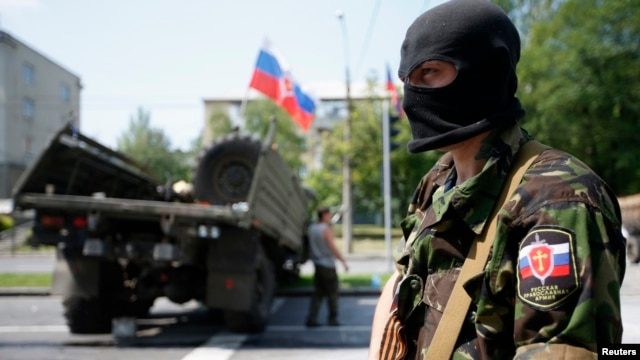 A member of a newly-formed pro-Russian armed group called the Russian Orthodox Army mans a barricade near Donetsk airport, May 29, 2014.