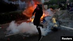 Seorang demonstran bentrok dengan polisi anti huru-hara dalam aksi protes di distrik Sha Tin, Hong Kong, Selasa (1/10).