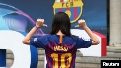 Seorang penggemar klub Barcelona mengenakan kaos dengan nomor punggung Lionel Messi sebelum laga penyisihan Grup B Liga Champion antara Barcelona melawan PSV Eindhoven, di Camp Nou, Barcelona, Spanyol, 18 September 2018.