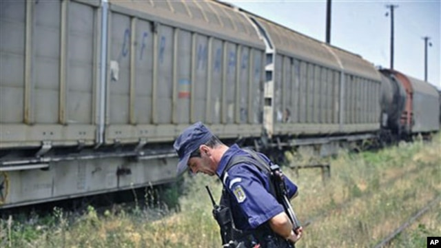 A Romanian gendarme stands next to a freight train that was transporting 64 Romanian-produced missile warheads, which authorities say have been stolen, in Giurgiu, southern Romania, July 17, 2011