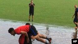 Pemain tim nasional AS, DeAndre Yedlin digendong pelatih Luis Ramirez melewati genangan air di sekitar lapangan tempat latihan, di Couva, Trinidad, Senin, 9 Oktober 2017.