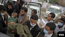 Petugas paramedik membawa korban yang terluka dalam demonstrasi ke sebuah klinikd darurat di Sana'a, Minggu (13/3).