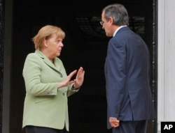 FILE - Greece's Prime Minister Antonis Samaras, right, and Germany's Chancellor Angela Merkel speak at the Maximos mansion in Athens, Oct. 9, 2012.