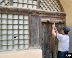 管理员给毛泽东旧居开门,左侧窗户上可以看到一个窟窿。