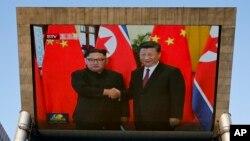Una pantalla gigante de TV muestra la reunión entre el líde de Corea del Norte, Kim Jong Un y el presidente de China, Xi Jinping en el Gran Salón del Pueblo en Beijing el martes, 19 de junio de 2018.