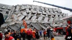 Nhân viên cứu hộ tìm kiếm nạn nhân trong một tòa nhà bị sập vì động đất ở Đài Nam, Đài Loan, 6/2/2016.