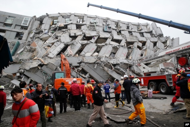 FILE - Rescue workers search a collapsed building from an early morning earthquake in Tainan, Taiwan, Feb. 6, 2016.