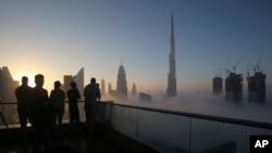FILE - Photographers take pictures as the sun rises over the city skyline with the Burj Khalifa, world's tallest building at the backdrop, seen from a balcony on the 42nd floor of a hotel on a foggy day in Dubai, United Arab Emirates, Dec. 31, 2016. (AP Photo/Kamran Jebreili)
