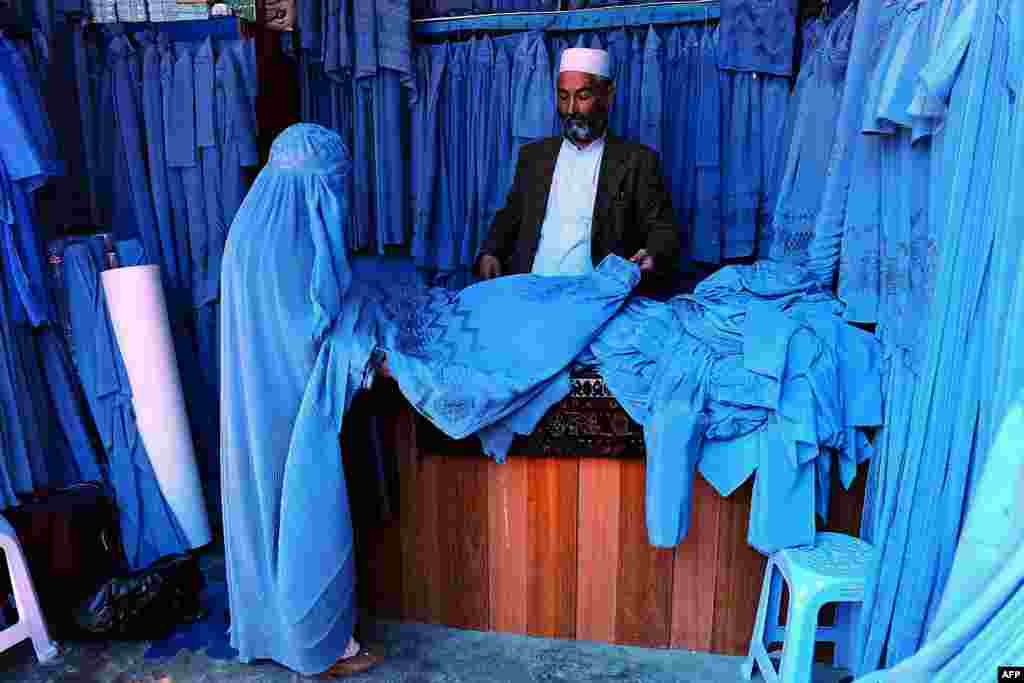 An Afghan shopkeeper shows a selection of burqas to a customer at a bazaar in Herat, April 13, 2014