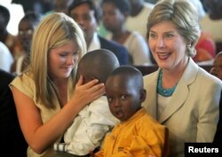 FILE - United States first lady Laura Bush and daughter Jenna, left, hold Rwandan children they met at an AIDS project during a church service at Kagarama Church in Kigali, July 14, 2005. Bush was on the last leg of her official visit to Africa after the meeting of G8 leaders in Gleneagles, Scotland.