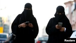 FILE - Saudi women use the Careem app on their mobile phones in Riyadh, Saudi Arabia, Jan. 2, 2017.Saudi Arabia is well known as the world's most gender-segregated nation, where women live under the supervision of a male guardian, cannot drive, and in public must wear head-to-toe black garments.