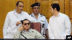 Mantan Presiden Mesir Hosni Mubarak, duduk, bersama dua putranya Gamal Mubarak (kiri) dan Alaa Mubarak (kanan) pada sidang di Akademi Polisi, Kairo, Sabtu (14/9).