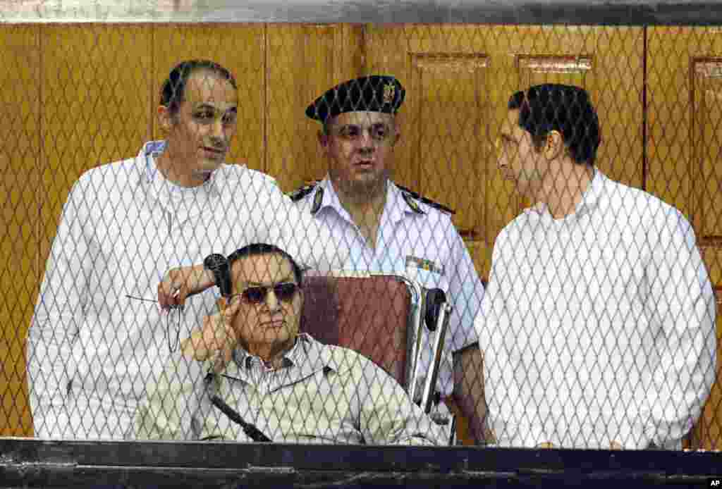 Former Egyptian President Hosni Mubarak, seated, and his two sons Gamal Mubarak, left, and Alaa Mubarak, right, attend a hearing in a courtroom at the Police Academy, Cairo.
