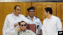 Former Egyptian President Hosni Mubarak, seated, and his two sons Gamal Mubarak, left, and Alaa Mubarak, right, Cairo, Egypt, Sept. 14, 2013.