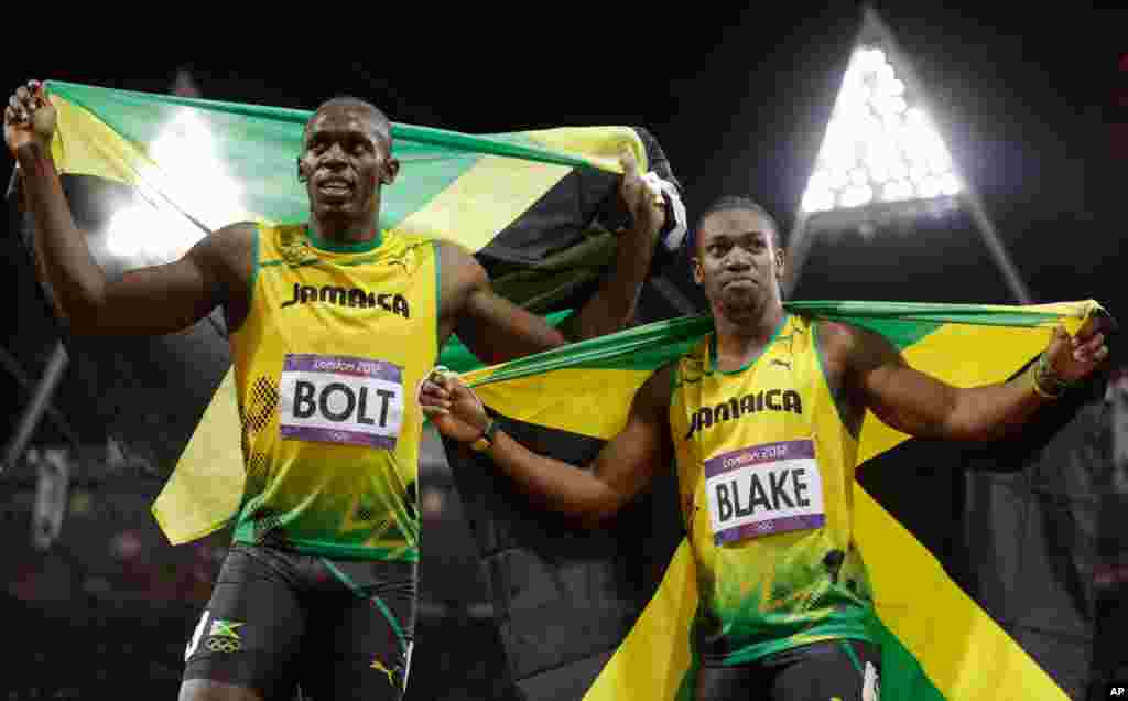 Usain Bolt celebrates winning gold alongside silver medalist Yohan Blake, both of Jamaica, following the men's 100-meter final.