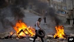 在以色列军队袭击西岸城市纳布卢斯期间,巴勒斯坦人焚烧轮胎。(2015年10月6号)