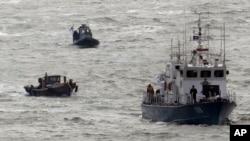 지난 2011년 3월 한국 연평도 인근에서 한국 해경선(오른쪽)이 북한 주민이 타고 넘어온 목선(왼쪽 아래)를 견인하고 있다. (자료사진)