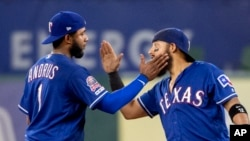 FILE - Texas Rangers baseball players Elvis Andrus (left) and Rougned Odor playfully slap each other to celebrate their 5-0 win over the Houston Astros in a baseball game, July 11, 2019, in Arlington, Texas. (AP Photo/Jeffrey McWhorter)