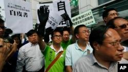 2014年6月11日香港中国联络处外抗议者举着模拟《白皮书》示威。