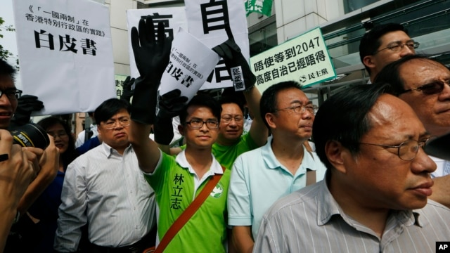 """Protesters raise a mock """"white paper"""", left, released by Beijing State Council on Tuesday saying it holds ultimate control over the former British colony, outside the Chinese liaison office in Hong Kong, June 11, 2014."""