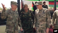 FILE - U.S. Gen. John Nicholson, top U.S. commander in Afghanistan, left, talks with Col. Khanullah Shuja, commander of the Afghan special operations force, and U.S. Gen. Joseph Votel, head of U.S. Central Command, at Camp Morehead in Afghanistan, Aug. 20, 2017.