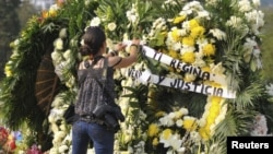 Seorang fotografer meletakkan karangan bunga di tempat pemakaman Regina Martinez, wartawan dan koresponden Majalah Meksiko Proceso di Xalapa (30/4).