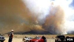 Los gigantescos incendios en Arizona atraen la atención de quienes transitan por la ruta 92, en las montañas Huachuca, cerca de Sierra Vista, Arizona.