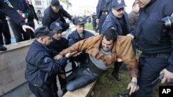Algerian policemen detain a protester during a demonstration in Algiers, February 12, 2011