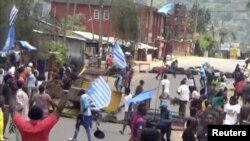 FILE - A still image taken from a video shot on Oct. 1, 2017, shows protesters waving Ambazonian flags in front of road block in the English-speaking city of Bamenda, Cameroon.