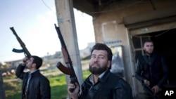 Pejuang Tentara Pembebasan Suriah (Free Syrian Army) memandang ke arah pesawat tempur angkatan udara Suriah, yang tidak tampak di gambar, di desa Fafeen, utara Provinsi Aleppo, Suriah, 11 Desember 2012.